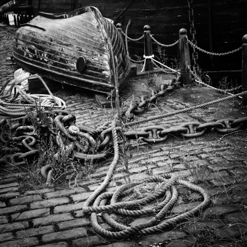Monochrome (black and white) image of upturned small boat and rope on Victoria Dock, Dundee, Scotland. DD006