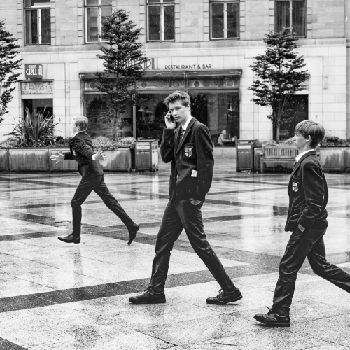 Monochrome (black and white) image of three pupils of Dundee High School in City Square, Dundee after the school's graduation ceremony in the Caird Hall. DD007