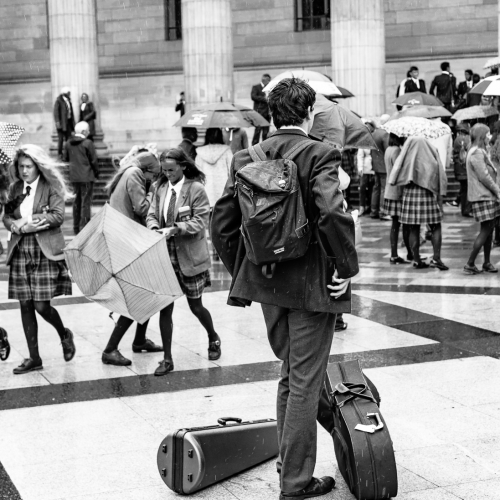 Monochrome (black and white) image of a pupil of Dundee High School in City Square, Dundee after the school's graduation ceremony in the Caird Hall. DD008