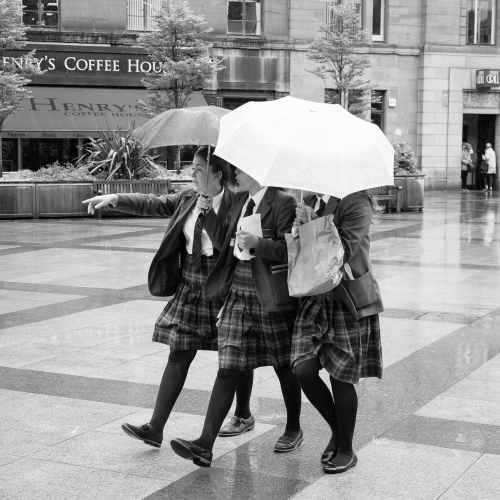Monochrome (black and white) image of three pupils of Dundee High School in City Square, Dundee after the school's graduation ceremony in the Caird Hall. DD009