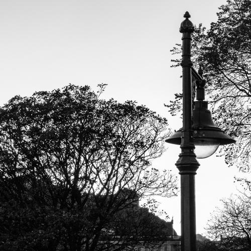 Monochrome (black and white) image of iron lamp-post and Edinburgh Old Town, from Waverley Bridge, Edinburgh, Scotland, United Kingdom.