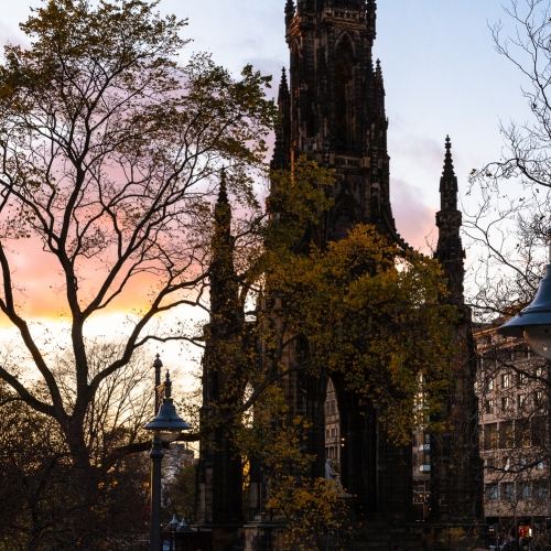 Iron lamp-posts and the Scott Monument at dusk from Waverley Bridge, Edinburgh, Scotland, United Kingdom.