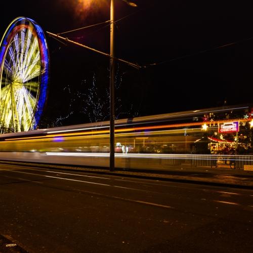 Light trails and a giant Ferris Wheel in Princes Street on New Years Day, Edinburgh, Scotland, United Kingdom.