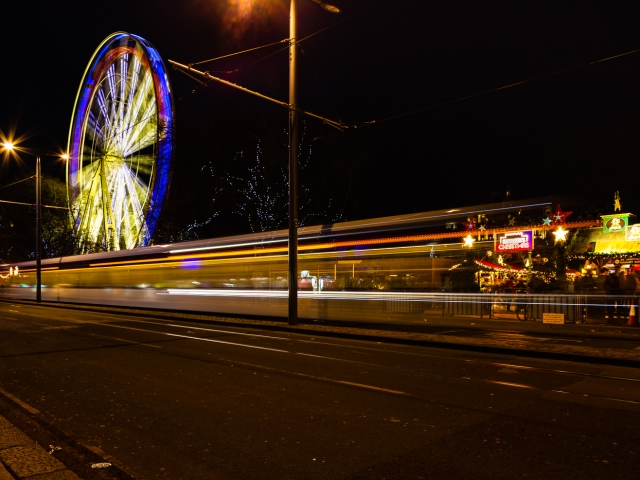 Light trails and a giant Ferris Wheel in Princes Street on New Years Day, Edinburgh, Scotland, United Kingdom.