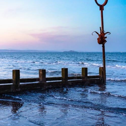 Groyne and marker post at Portobello beach, Edinburgh, Scotland, United Kingdom.