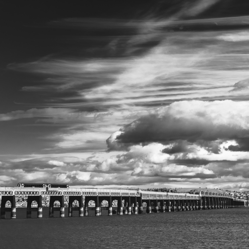 Monochrome image of clouds gathering over the Tay Rail Bridge from Dundee, Scotland. DD048