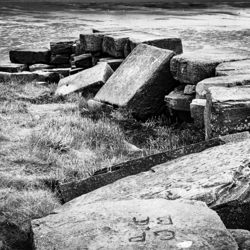 Monochrome (black and white) image of derelict stone pier at Invergowrie, Scotland. DD104