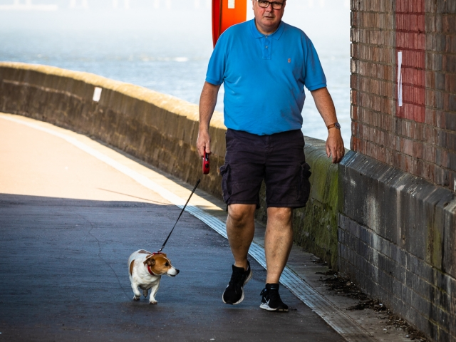 Large man and small dog walking under arch at Dundee end of the Tay Rail Bridge, Scotland. DD085