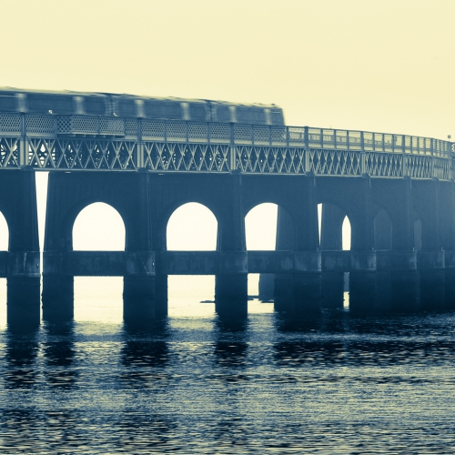 Duotone image of the Tay Railway Bridge as a train passes over, Dundee, Scotland. DD079