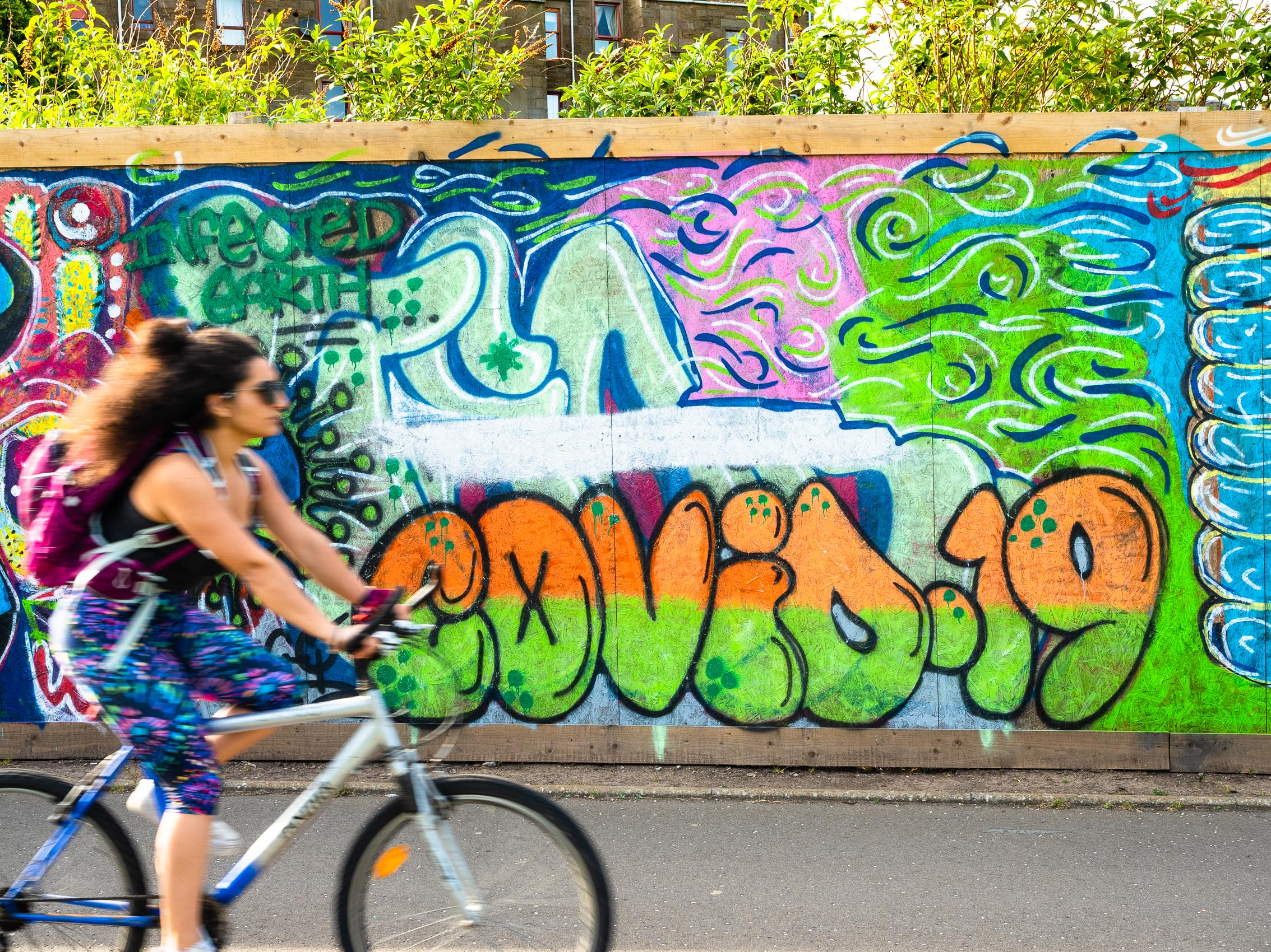Young woman cycling past Covid-19 graffitti artwork in Dundee, Scotland. DD065