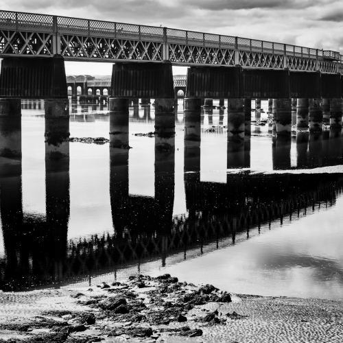 Monochrome (black and white) image of the Tay Railway Bridge at low tide, Dundee, Scotland. DD076