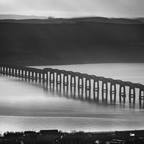 Monochrome (black and white) image of the Tay Rail Bridge from Dundee Law, Dundee, Scotland, United Kingdom.