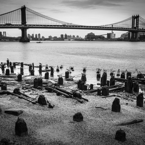 Manhattan Bridge from the shore of the East River, Manhattan, New York City, NY, USA.