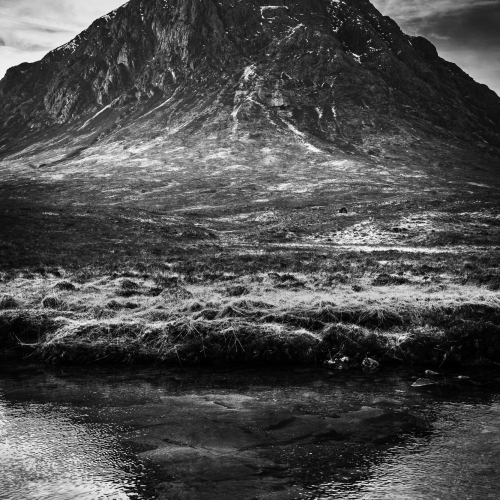 Buachaille Etive Mor casts a shadow in the River Coupall, Rannoch Moor, Scotland.