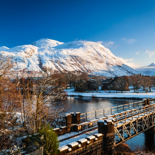 Ben Nevis and the railway bridge carrying the Mallaig Line over the River Lochy, Scotland.