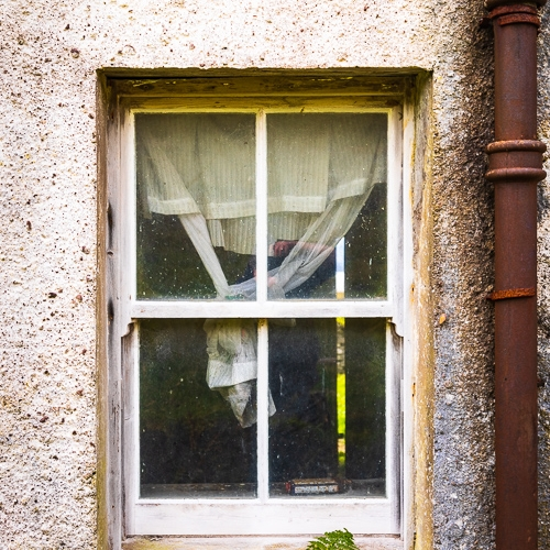Curtained window of an abandoned croft house, near Callakille, Scotland. AP020