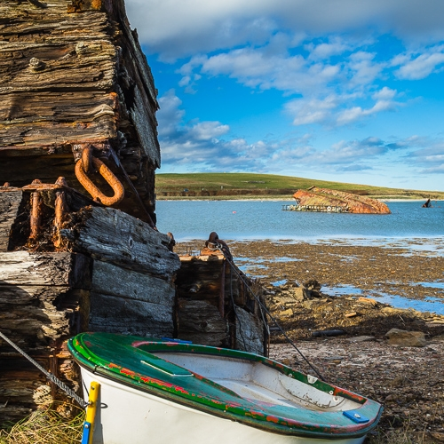 Wooden piles and beached boat between Burray and Glimps Holm, Orkney Islands. OR017