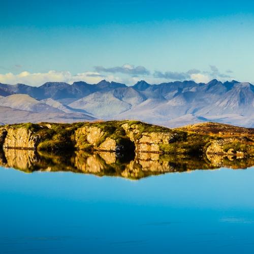 The Cuillins of Skye viewed from a lochan near the Bealach na Ba, Applecross, Scotland. AP014